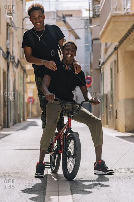 Happy youthful African American male teenagers having fun while riding on BMX bike together in street