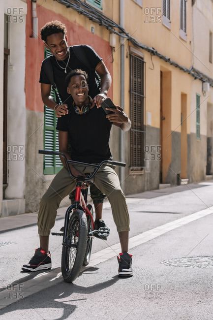 Happy youthful African American male teenagers taking selfie on cellphone while sitting on BMX bike together in street
