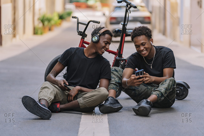 Cheerful youthful African American male teenager sharing pictures on cellphone with joyful black male friend in headphones while sitting together on asphalt road in street