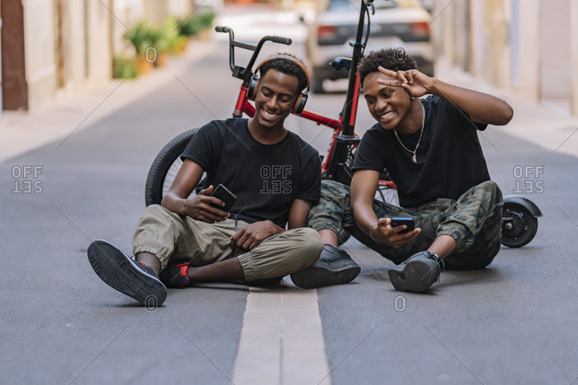 Cheerful youthful African American male teenager taking selfie pictures on cellphone with joyful black male friend in headphones while sitting together on asphalt road in street