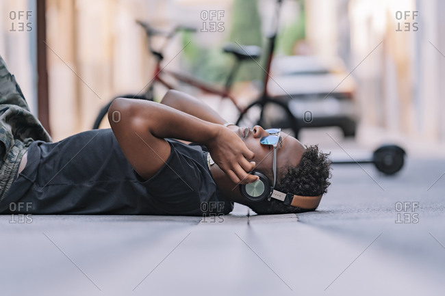 Side view of serious youthful African American man in sunglasses and headphones listening to music while lying on asphalt road in street