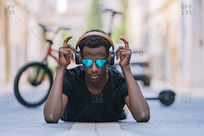 Concentrated youthful African American man in sunglasses wearing headphones and listening to music while lying on asphalt road in street