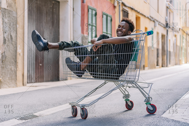 Side view of pensive youthful African American male teenager in casual clothes looking at camera while sitting in metal shopping trolley in street