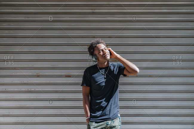 Stylish modern African American man with closed eyes and headphones listening to music at striped wall in street