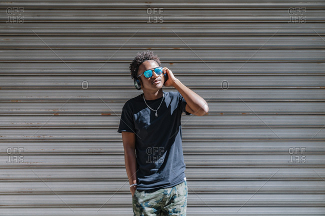 Stylish modern African American man in sunglasses and headphones listening to music at striped wall in street