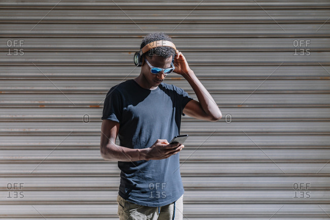Stylish modern African American man in sunglasses and headphones listening to music on the mobile phone at striped wall in street