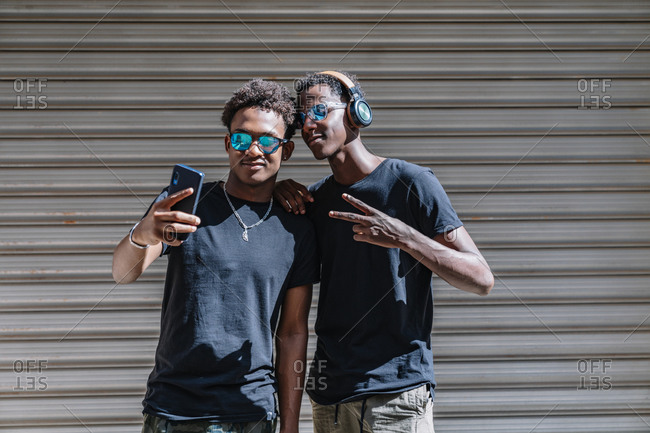 Cool youthful African American male teenagers in sunglasses taking picture with mobile phone while standing in sunlight in street