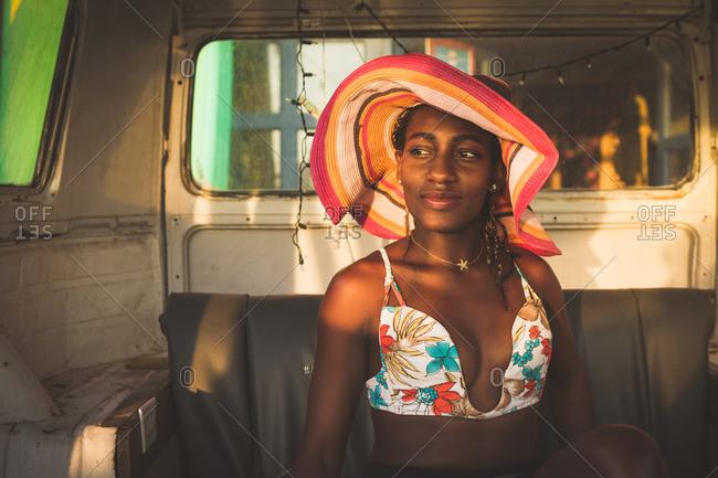 Happy African American female sitting behind wheel of car
