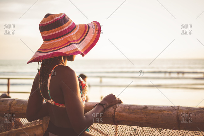 Side view of relaxed young African American female in colorful wide brimmed striped hat and bikini top standing at wooden fence on beach and enjoying seascape