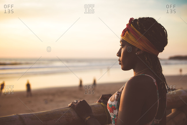 Woman in hat standing on beach and enjoying seascape