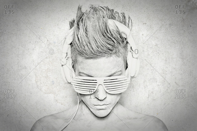 Serious youthful short haired female in headphone set and shutter shades sunglasses with naked shoulders listening music in studio
