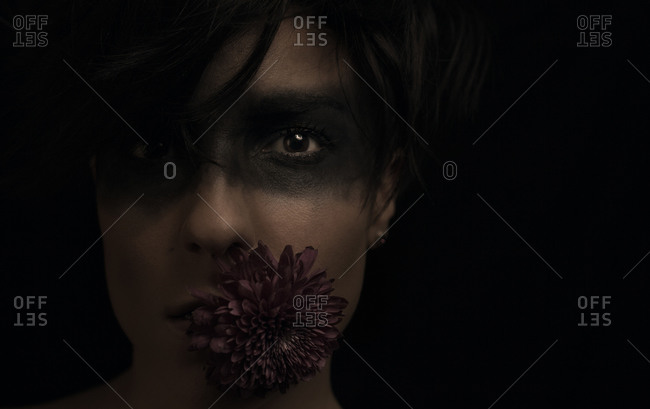 Crop thoughtful young dark haired female model with black color around eyes and flower in mouth looking at camera in studio on black background