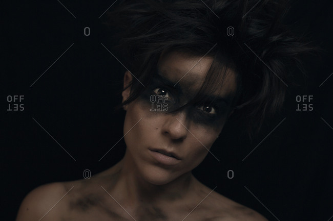 Pensive young dark haired female model with uncombed hair and black make up around eyes looking at camera in studio on black background