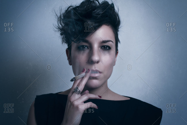 Unhappy pensive crying female with dark short hair and in black clothes looking at camera and smoking cigarette in studio on gray background