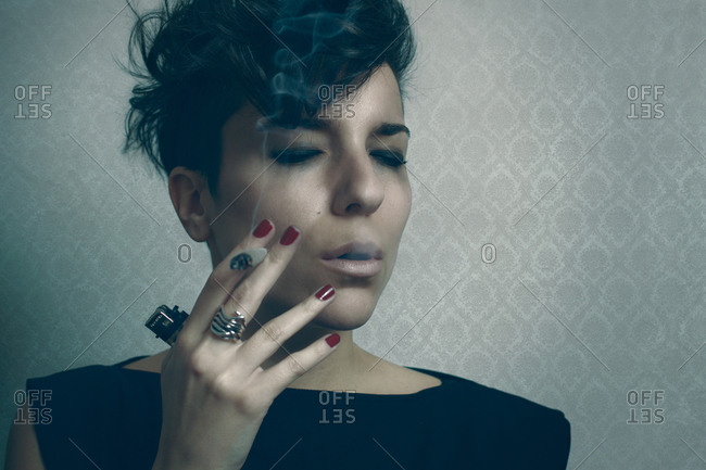 Upset woman smoking cigarette in studio