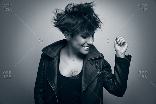 Strong young female rocker in leather jacket in studio