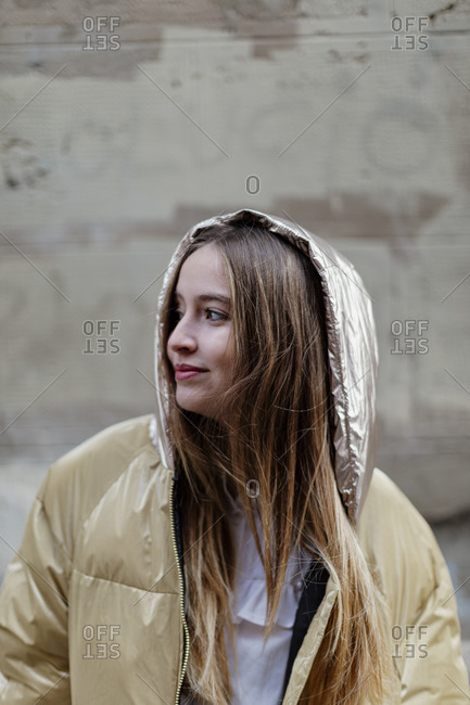 Young blonde woman wearing golden colored jacket