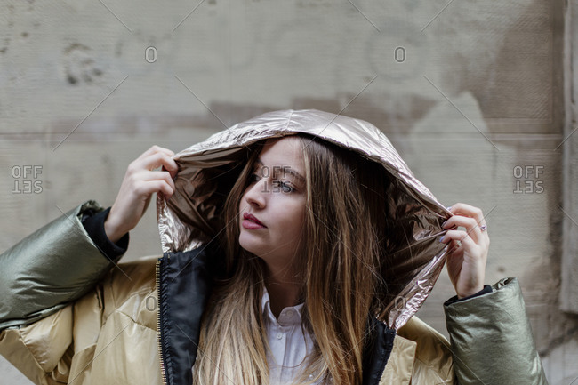 Young blonde woman putting up hood on her golden colored jacket