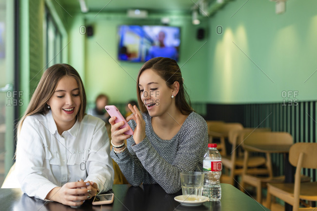 Girls texting on cell phone while sitting in cafe
