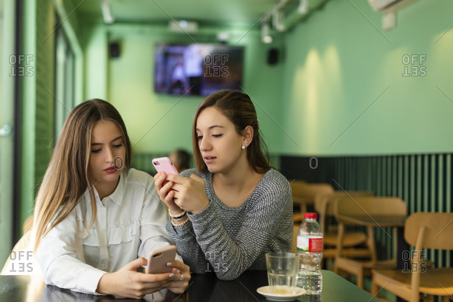 Two girls texting on cell phone while sitting in cafe