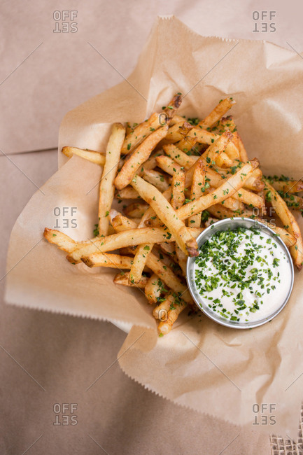 Overhead view of French fries with sauce and chives