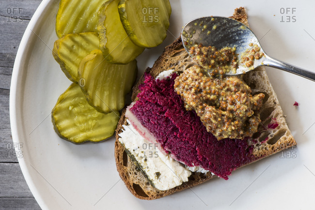 Beet mousse, goat cheese and seeded mustard on toast with pickles