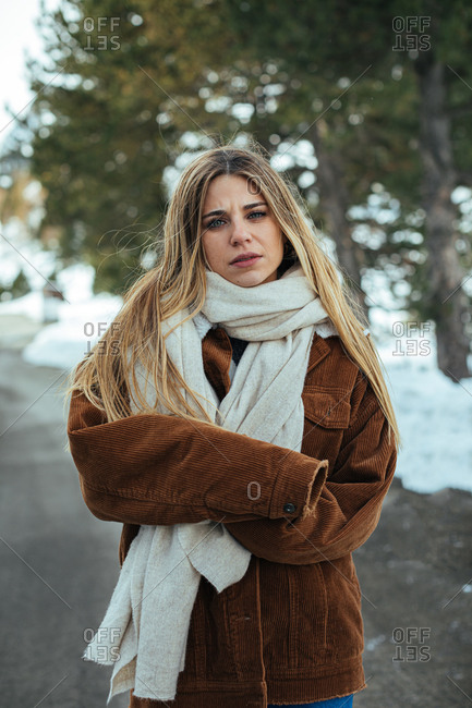 Portrait of blonde woman wearing scarf and corduroy jacket on a snowy mountain road
