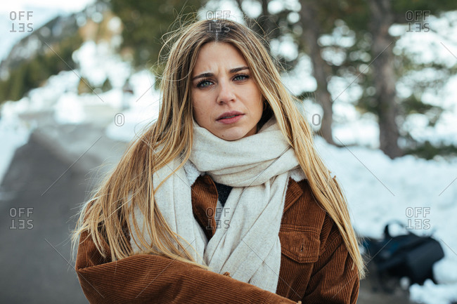 Close up of blonde woman wearing scarf and corduroy jacket on a snowy mountain road