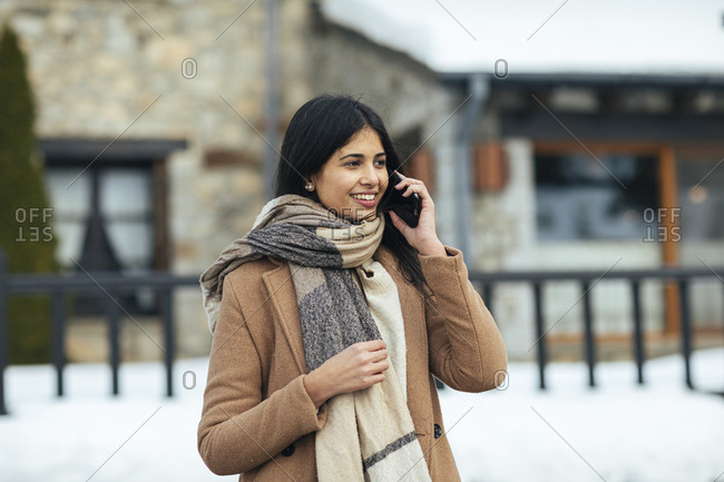 Woman wearing scarf and tan peacoat talking on cell phone while outdoors in winter