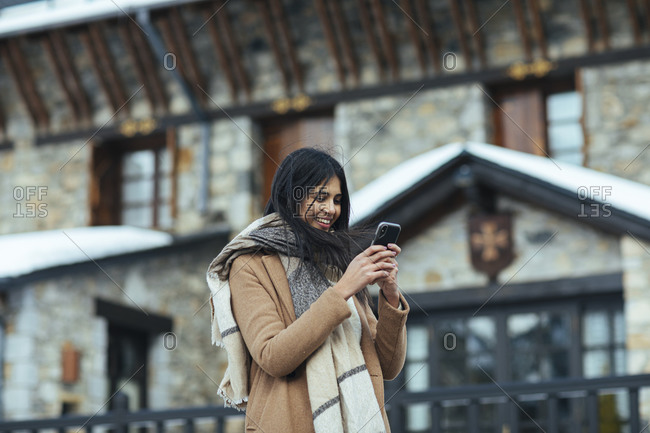 Woman wearing scarf and tan peacoat using cell phone while outdoors in winter