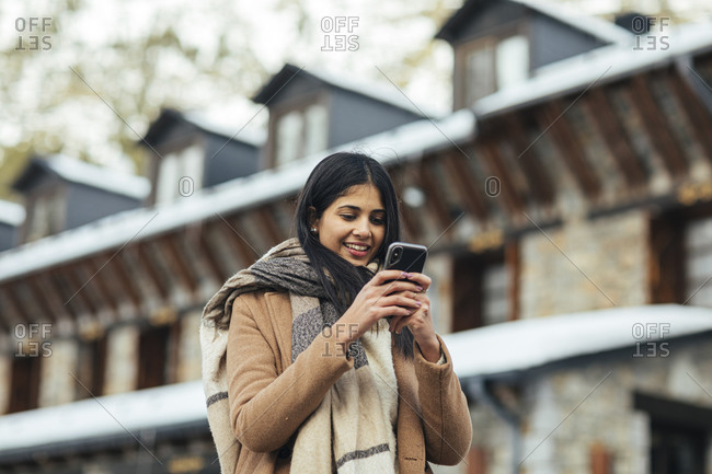 Woman wearing scarf and tan peacoat texting on cell phone while outdoors in winter