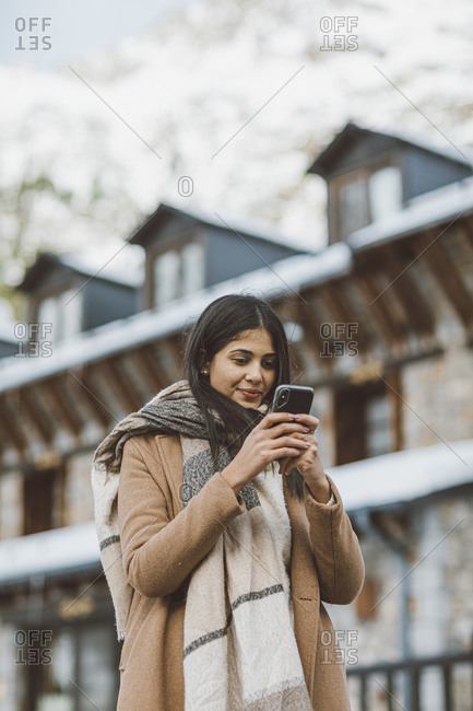 Young woman wearing scarf and tan peacoat texting on cell phone while outdoors in winter