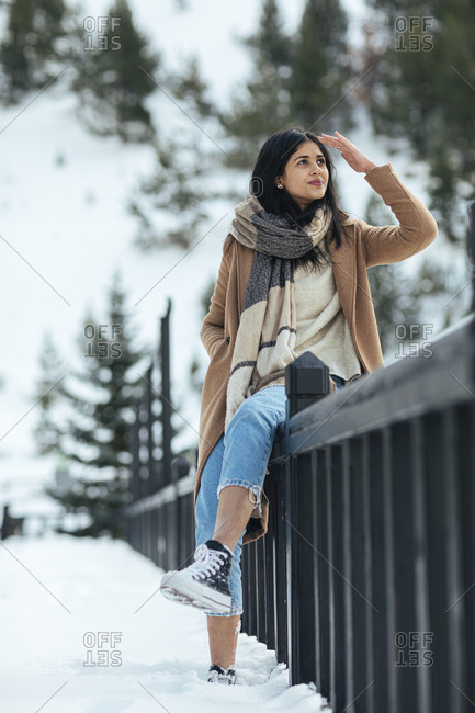 Woman wearing scarf and tan peacoat while leaning on railing looking out a snowy mountain