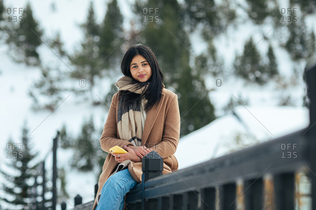 Woman wearing scarf and tan peacoat while leaning on railing on a snowy mountain