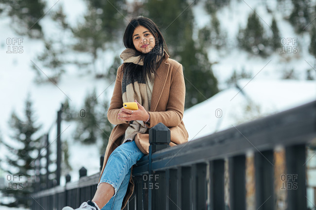 Portrait of woman wearing scarf and tan peacoat while leaning on railing on a snowy mountain