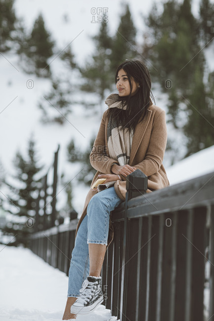 Woman wearing scarf and tan peacoat sitting on railing on a snowy mountain