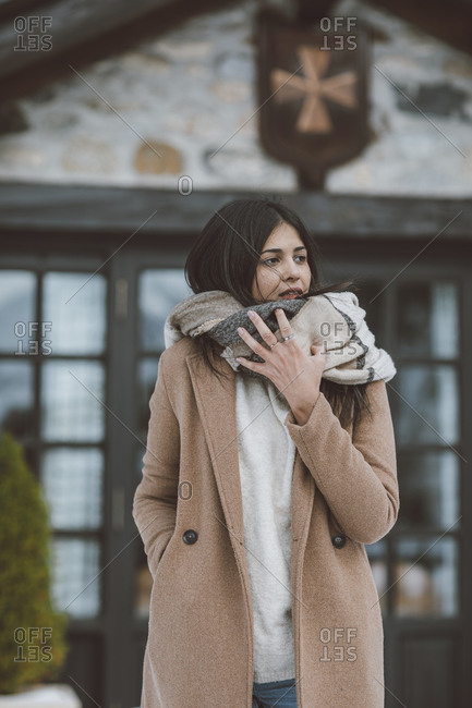 Young woman bundled up in a scarf while outside building in winter