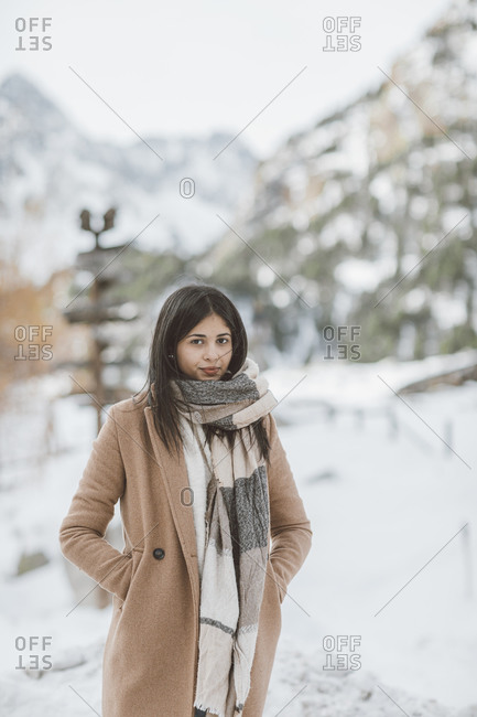 Woman wearing scarf and tan peacoat on a snowy mountain