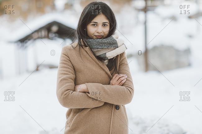 Woman wearing scarf and tan peacoat crossing arms on a snowy mountain