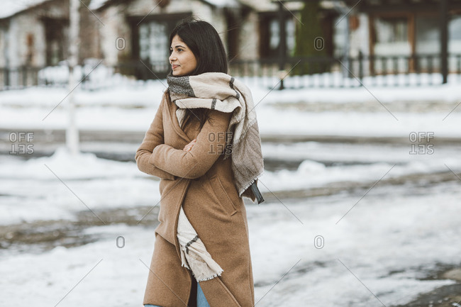 Woman wearing scarf and tan peacoat crossing arms while walking on a snowy street