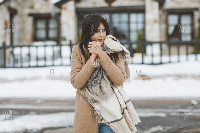 Young woman bundled up in a large scarf outside of a building in winter