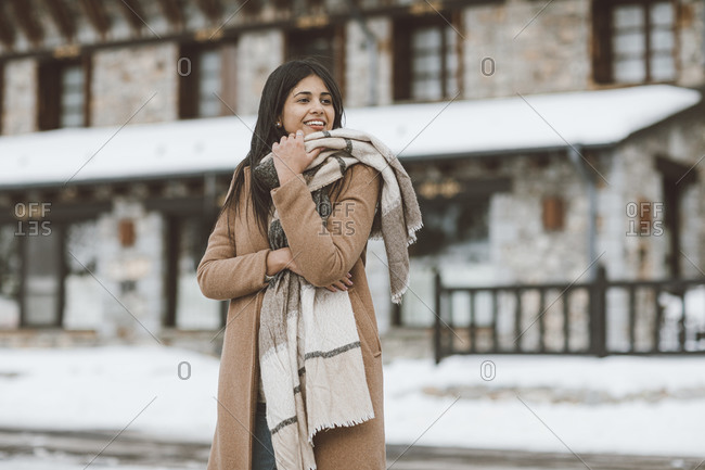 Stylish woman bundled up in a large scarf outside of a building in winter