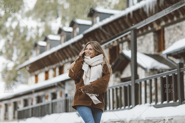 Smiling woman wearing scarf and corduroy jacket talking on phone while walking on a snowy street
