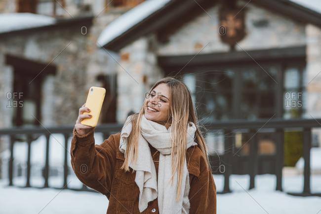 Blonde woman wearing a corduroy jacket taking a selfie outside in winter