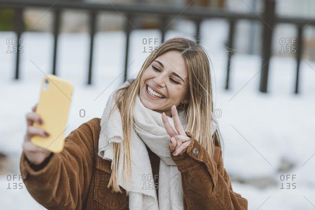 Woman wearing a corduroy jacket taking a selfie outside in winter