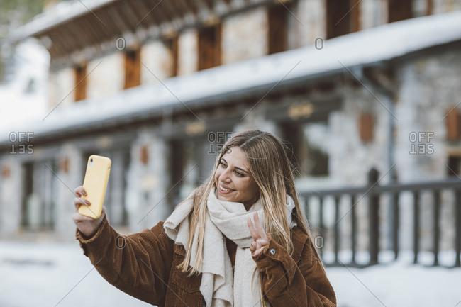 Young blonde woman wearing a corduroy jacket taking a selfie outside in winter