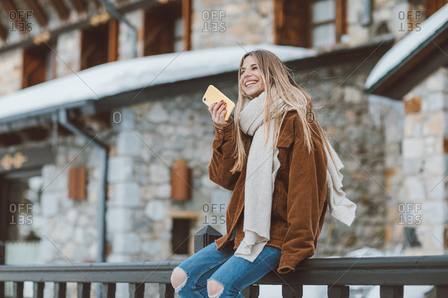Blonde woman wearing a corduroy jacket talking on phone outside of building in winter