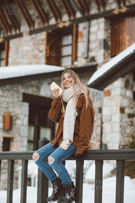 Blonde woman talking on phone outside of building in winter