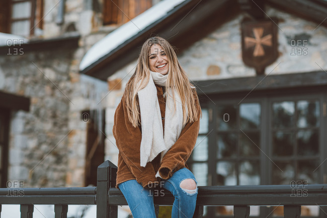 Portrait of a blonde woman sitting on railing outside of building in winter