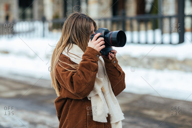 Young blonde woman taking photos on snow road in winter